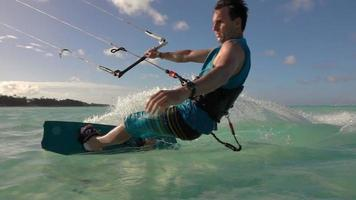 SLOW MOTION: Young surfer man has fun kitesurfing in island lagoon at sunset