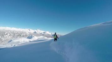 glücklicher Snowboarder, der Spaß hat, Pulverschnee-Hinterland in den schneebedeckten Bergen zu reiten