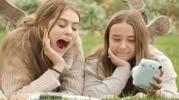 utilizzando la fotocamera polaroid retrò per scattare foto selfie due ragazze adolescenti che si divertono video