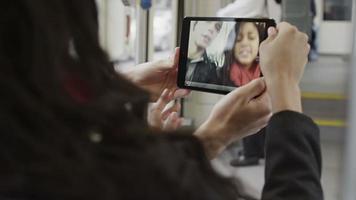 um casal se diverte no ônibus usando seu tablet para tirar fotos