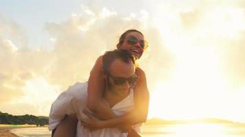 Joven pareja romántica se divierte al atardecer en la orilla en verano al aire libre - imágenes de video de gimbal steadicam hd