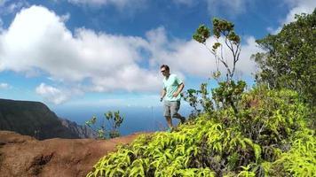 Cámara lenta: deportista trotando en las montañas de la selva con vistas al valle y al océano