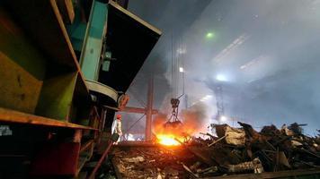 trabalhadores controlando a fundição de ferro na fornalha