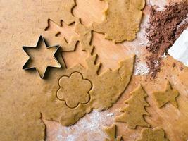 Formas de galletas y masa de pan de jengibre sobre tablero de pastelería de madera foto
