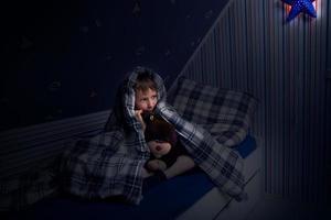 Kind versteckt sich unter der Decke photo
