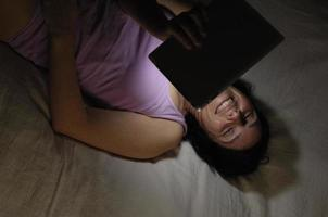 Woman with tablet in bed