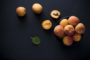 Fresh organic apricots on black background