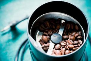 Electrical coffee-mill machine with roasted coffee beans photo
