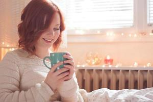 Young redhead woman in home interior.