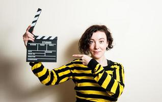 Girl smiling pointing out movie clapper on white background