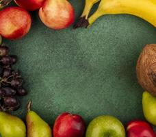 Assorted fruit border on green background