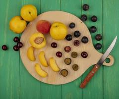 Assorted fruit on wooden plank and green background