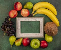 Assorted fruit around wooden frame on green background