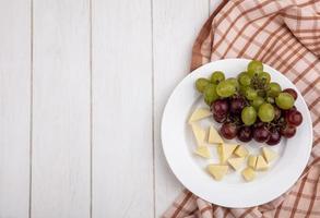 Plato de fruta y queso sobre fondo de madera con espacio de copia