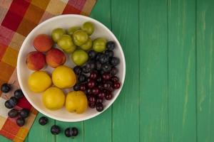 Assorted fruit in a dish on green background