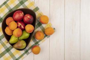 fruta variada sobre tela escocesa y fondo neutro