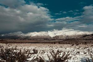 Snow covering grass and mountains