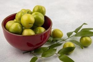 Ciruelas verdes en un recipiente con hojas sobre fondo blanco. foto