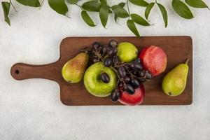 Surtido de frutas sobre tabla de cortar y fondo neutro