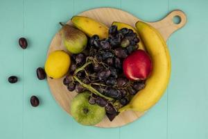 Assorted fruit on cutting board on blue background