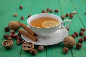 Cup of tea with lemon with nuts on green background
