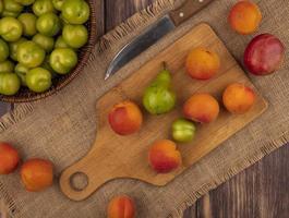 Surtido de frutas sobre tabla de cortar sobre fondo de madera