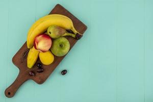 Surtido de frutas en la tabla de cortar sobre fondo azul.