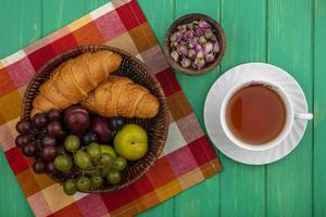 Assorted fruit and bread on stylized green background