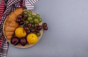 Assorted fruit and bread on neutral background