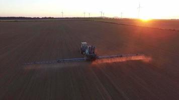 Tracteur faisant un pulvérisateur au coucher du soleil