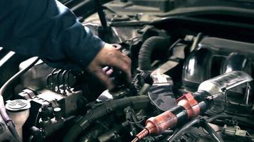 le mécanicien verse de l'huile fraîche dans le moteur