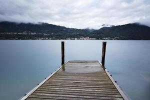 Tranquil scene of old wooden pier and misty Italian Alps