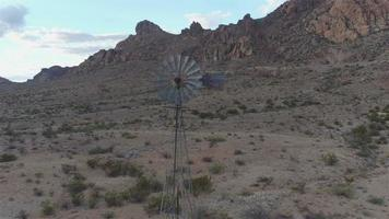 AERIAL: Big vintage windmill under beautiful rocky mountains