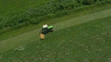 AERIAL: Tractor mowing in a big grass field