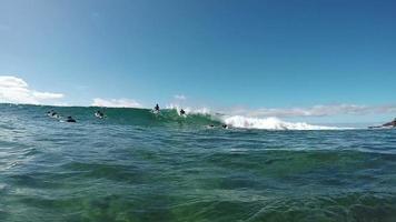Cámara lenta bajo el agua: chico joven surfista montando olas grandes