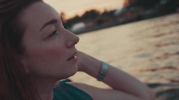 garota de cabelo vermelho bonito em barco a motor. noite de Verão. natureza. pôr do sol. tocar cabelo