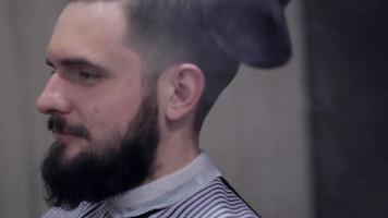 Male barber make a haircut for bearded client and using a talc at barbershop