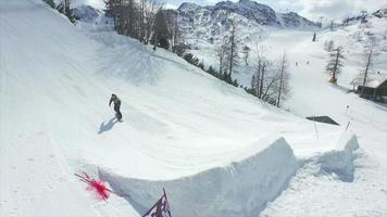 Antena: snowboarder profesional saltando gran salto en el parque de nieve