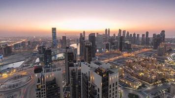 vista aérea panorâmica de uma grande cidade moderna do dia para a noite timelapse. baía comercial, dubai, emirados árabes unidos