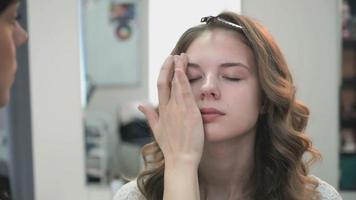rostro maestro haciendo maquillaje para modelo joven video