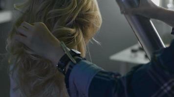 femmina bionda nel parrucchiere. parrucchiere sullo sfondo video