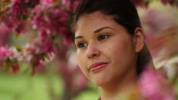 bela jovem sorrindo, rodeada de flores