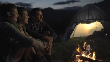 Group of three friends talking, smiling and warming with camp-fire in nature mountain outdoor camping scene at night close-up - HD video footage