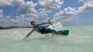 Cámara lenta de cerca: surfista alegre se divierte practicando kitesurf en el mar de la isla exótica