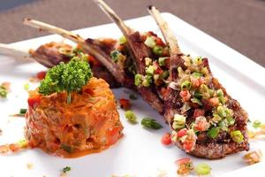 Grilled lamb ribs with herbal sauce on white ceramic tray