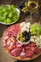 Antipasto catering platter with bacon, jerky, salami, cheese and grapes