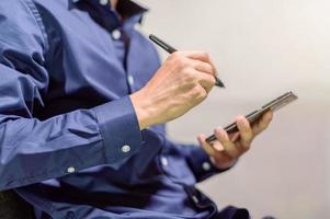 empresario con un teléfono inteligente y un bolígrafo para tomar notas