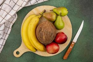 Assorted fruit on cutting board on green background