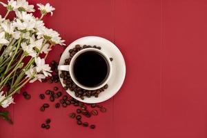 Coffee with flowers on red background with copy space