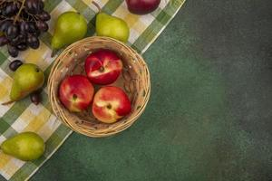 Fruta variada sobre tela escocesa y fondo verde